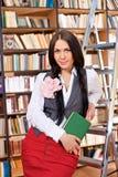 Estudiante bonito con el libro en biblioteca Fotos de archivo