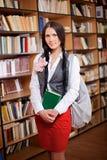 Estudiante bonito con el libro en biblioteca Foto de archivo