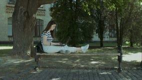 Estudiante bonito con el ordenador portátil que se sienta en el banco metrajes