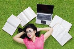 Estudiante bonito con el ordenador portátil y los libros en hierba Fotografía de archivo libre de regalías