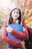 Estudiante bonito con el suéter en el parque del otoño Foto de archivo libre de regalías