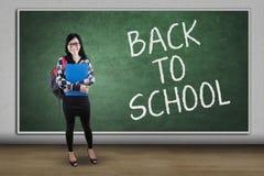 Estudiante bonito con el texto de nuevo a la escuela Foto de archivo