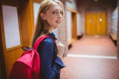 Estudiante bonito con la mochila que mira la cámara Imagen de archivo