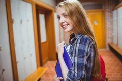 Estudiante bonito con la mochila que mira la cámara Fotos de archivo