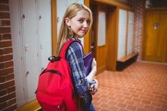Estudiante bonito con la mochila que mira la cámara Foto de archivo libre de regalías