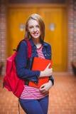Estudiante bonito con la mochila que mira la cámara Fotografía de archivo