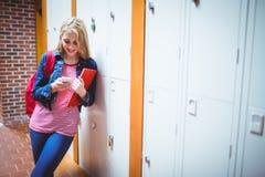Estudiante bonito con la mochila que se inclina contra el armario Imagenes de archivo