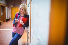 Estudiante bonito con la mochila que se inclina contra el armario Fotografía de archivo