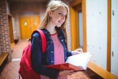 Estudiante bonito con la mochila que sostiene el cuaderno que mira la cámara Foto de archivo
