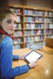 Estudiante bonito con los auriculares usando la tableta en biblioteca Foto de archivo