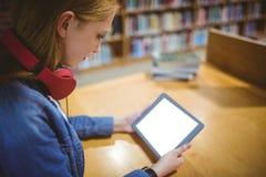 Estudiante bonito con los auriculares usando la tableta en biblioteca Imagenes de archivo