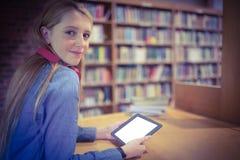 Estudiante bonito con los auriculares usando la tableta en biblioteca Fotografía de archivo libre de regalías