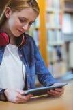 Estudiante bonito con los auriculares usando la tableta en biblioteca Fotos de archivo