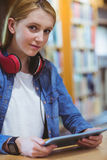 Estudiante bonito con los auriculares usando la tableta en biblioteca Imagen de archivo