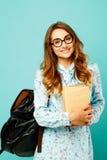 Estudiante bonito de los vidrios de la muchacha que lleva sonriente bonita que sostiene los libros Fotos de archivo libres de regalías