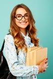 Estudiante bonito de los vidrios de la muchacha que lleva sonriente bonita que sostiene los libros Imagenes de archivo