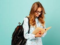 Estudiante bonito de los vidrios de la muchacha que lleva sonriente bonita que sostiene los libros Fotografía de archivo libre de regalías