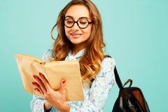Estudiante bonito de los vidrios de la muchacha que lleva sonriente bonita que sostiene los libros Foto de archivo libre de regalías