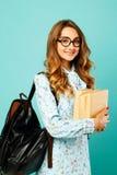 Estudiante bonito de los vidrios de la muchacha que lleva sonriente bonita que sostiene los libros Imagen de archivo libre de regalías