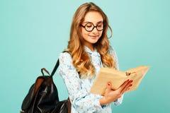 Estudiante bonito de los vidrios de la muchacha que lleva sonriente bonita que sostiene los libros Fotos de archivo