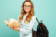 Estudiante bonito de los vidrios de la muchacha que lleva sonriente bonita que sostiene los libros Imagen de archivo