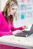 Estudiante bonito, femenino con la computadora portátil y libros Foto de archivo libre de regalías