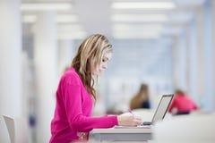Estudiante bonito, femenino con la computadora portátil y libros Fotos de archivo