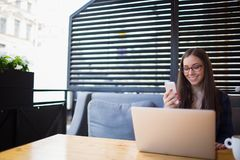 Estudiante bonito joven en vidrios que charla en red vía el teléfono móvil durante trabajo sobre el ordenador portátil portátil Imagen de archivo