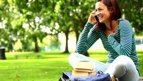 Estudiante bonito que habla en el teléfono en la hierba almacen de video
