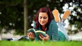 Estudiante bonito que miente en la hierba que lee un libro que escucha la música almacen de metraje de vídeo