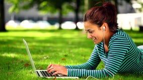 Estudiante bonito que miente en la hierba usando el ordenador portátil que escucha la música metrajes