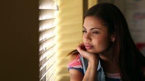 Estudiante bonito que mira hacia fuera la ventana almacen de video