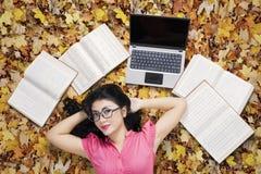 Estudiante bonito que se relaja en las hojas de otoño Imágenes de archivo libres de regalías