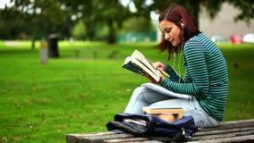 Estudiante bonito que se sienta en el banco que lee un libro que escucha la música almacen de metraje de vídeo