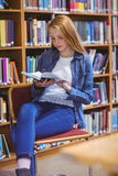 Estudiante bonito que se sienta en el libro de lectura de la silla en biblioteca Foto de archivo