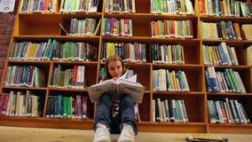 Estudiante bonito que se sienta en el libro de lectura del piso en la biblioteca almacen de metraje de vídeo