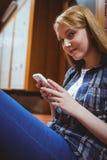 Estudiante bonito que se sienta en el piso contra la pared usando smartphone Fotografía de archivo