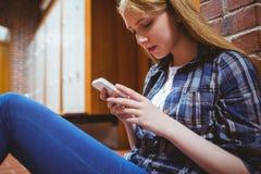 Estudiante bonito que se sienta en el piso contra la pared usando smartphone Imagen de archivo libre de regalías
