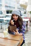 Estudiante bonito que se sienta en restaurante y colorete sus labios con el lápiz labial Foto de archivo