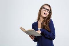 Estudiante bonito que sostiene el libro y que mira lejos Foto de archivo