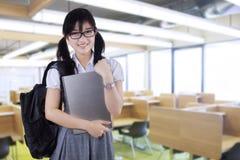 Estudiante bonito que sostiene el ordenador portátil en clase Imagen de archivo