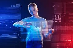 Estudiante bonito que sostiene una tableta transparente y que mira la pantalla de ella Foto de archivo libre de regalías