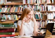 Estudiante bonito que usa el ordenador portátil en biblioteca Fotos de archivo