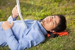 Estudiante With Book Lying en hierba en la universidad Fotografía de archivo libre de regalías