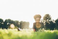 Estudiante brasileño joven sonriente en el césped fotografía de archivo libre de regalías
