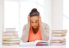 Estudiante cansado con los libros y las notas Foto de archivo libre de regalías