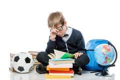 Estudiante cansado con un libro que presenta en un fondo blanco Imagen de archivo