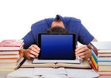 Estudiante cansado con una tableta Imagen de archivo libre de regalías