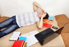 Estudiante cansado en el sofá Foto de archivo libre de regalías