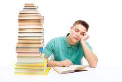 Estudiante cansado joven que se sienta en el escritorio con la alta pila de libros Imágenes de archivo libres de regalías